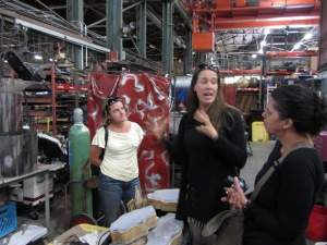 Catie Magee (left) and Jess Hobbs (center) explain their process to AbD researcher Jessica Ross (right) inside  Flux Foundation's workspace at American Steel Studios.