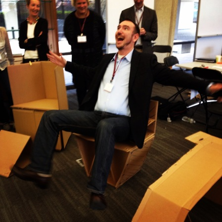 Success! Kicking your feet off the ground is the best way to prove a cardboard chair can hold your weight.
