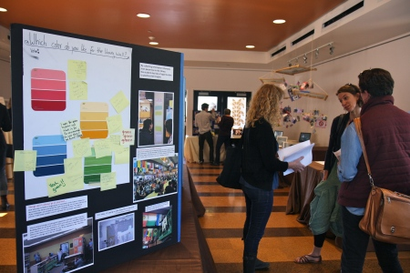 Teachers from various OLC schools discuss the array student work on display, including a library redesign project (left) at OIHS. Photo by Emi Kane.