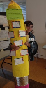 OLC member Carla Aiello of Emerson Elementary School posing with an over-sized pencil made by her kindergarten students.